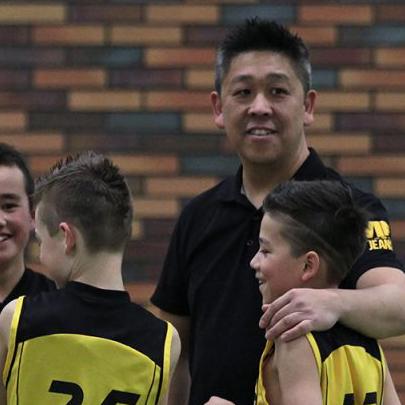 Ying Wai Man coaching a junior basketball team.
